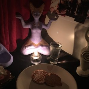 A photo of Heathwitch's Ancestors' Altar, October 2019. Upon a black altar cloth sits the statue of a Goddess sitting in the lotus position, her hands held at shoulder height, palms upward to the sky. Before her is a lit tealight candle and a shot glass full of water. In the foreground is a plate of biscuits, whilst behind her a photo collage of Heathwitch's Beloved Dead can be seen on the wall.